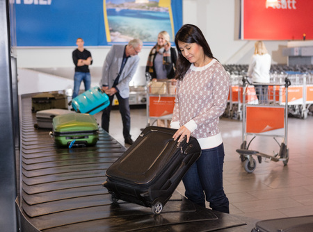 Woman Collecting Luggage At Conveyor Belt In Airport Archivio Fotografico