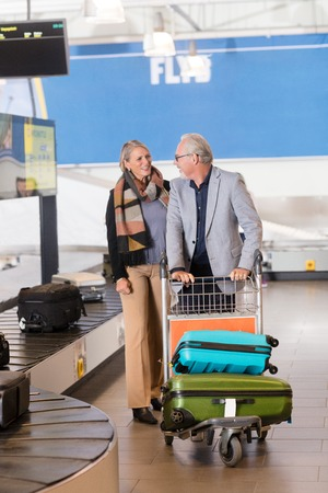 Senior Couple Collecting Baggage From Conveyor Belt At Airport