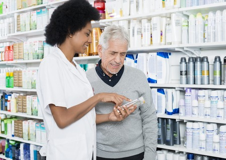 african business: Pharmacist Showing Information On Product To Customer