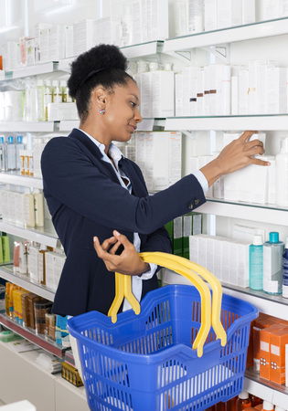 african business: Businesswoman Choosing Products In Pharmacy Stock Photo