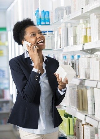 african business: Woman Holding Product While Communicating On Mobile Phone Stock Photo