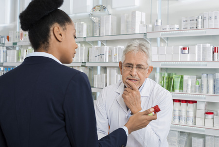 african business: Pharmacist And Businesswoman Discussing Over Medicine