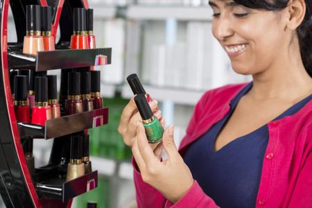 Smiling Woman Choosing Nail Polish In Pharmacy