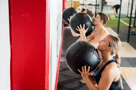 Woman And Man Throwing Medicine Ball In Gym