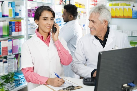 Chemist Looking At Female Colleague Using Telephone At Counter Foto de archivo