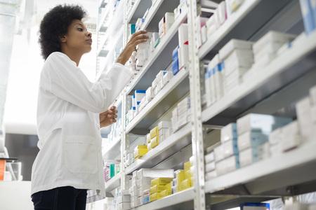 químico de sexo femenino de la organización en los estantes en farmacia