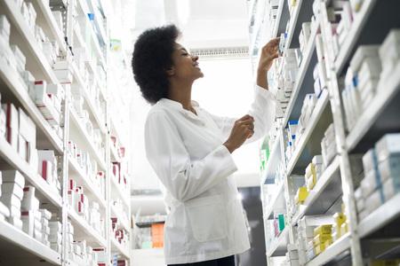 sonriendo químico hembra de la elección de los productos en el estante en la farmacia
