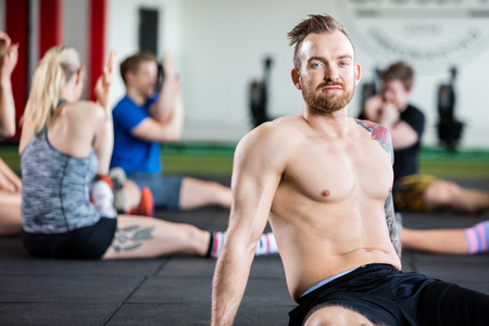 Confident Instructor Sitting While Clients Exercising