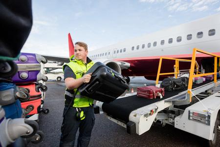 Werknemer Stacking Bags On Trailer At Runway
