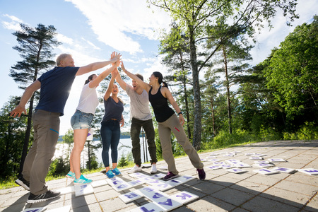Friends Giving High-Five After Solving Crossword Puzzle On Patio Zdjęcie Seryjne