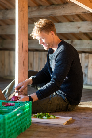 Man Cutting Onion While Sitting In Shed