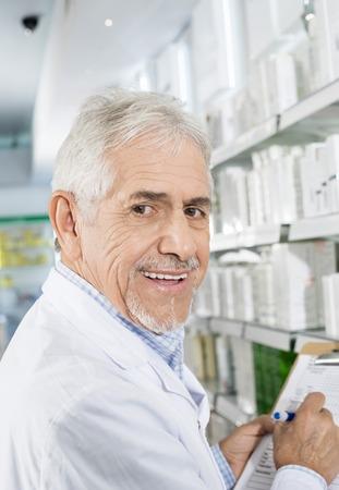Smiling Senior Pharmacist Counting Stock In Drugstore