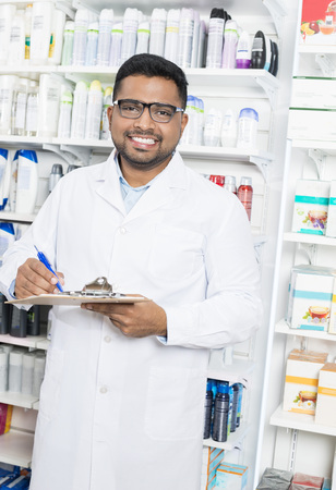 Smiling Pharmacist Writing On Clipboard In Pharmacy