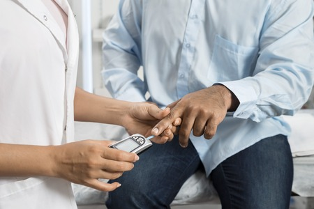 Female Doctor Examining Patients Sugar Level With Glucometer