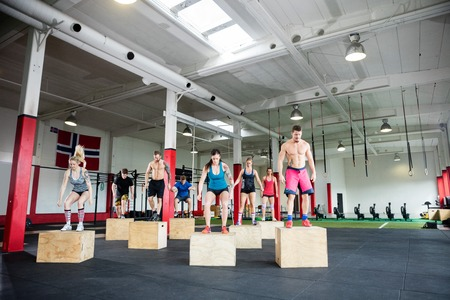Male And Female Clients Performing Box Jumps