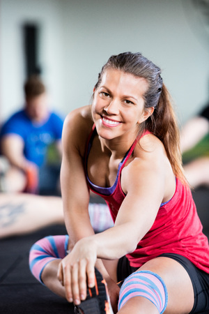 Portrait Of Smiling Woman Doing Stretching Exercise