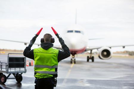 Señalización del equipo de tierra al avión en la pista mojada Foto de archivo - 87902249
