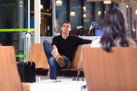 Man Sitting On Chair In Waiting Room At Airport Stock Photo