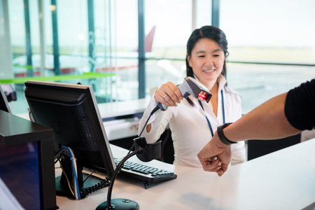 Smiling Receptionist Scanning Smart Watch Of Passenger At Airpor