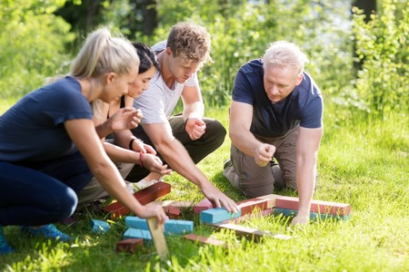 Friends Planning While Stacking Building Blocks On Grassy Field
