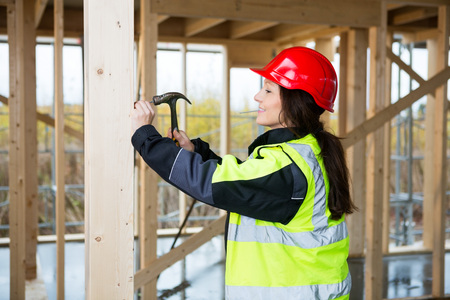 Female Carpenter In Reflective Jacket Hammering Nail In Wood