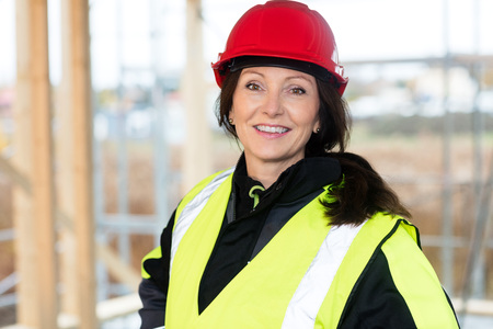 Confident Female Carpenter In Protective Wear At Site Stock Photo
