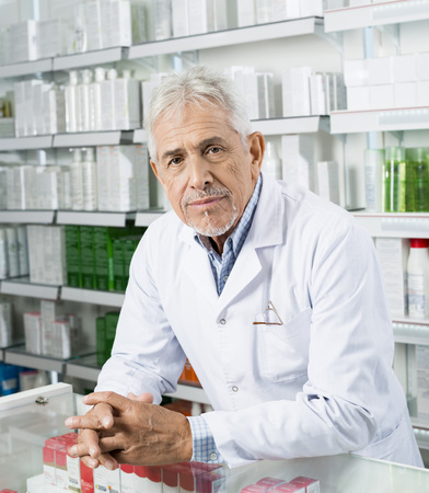 Confident Chemist Leaning On Counter In Pharmacy