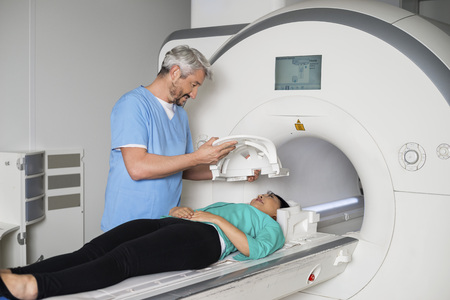 Doctor que prepara al paciente para la exploración del CT