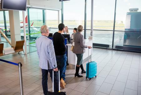 Passagiers met bagage wachten op hun beurt op luchthavenrecept