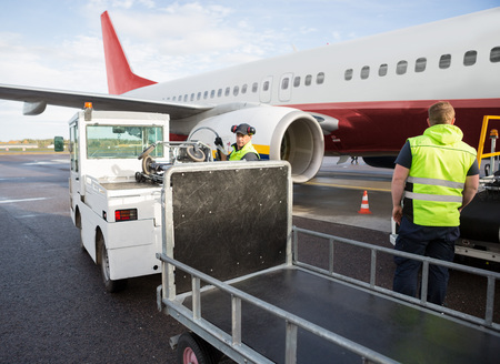Ground Staff Working By Airplane And Truck On Runway