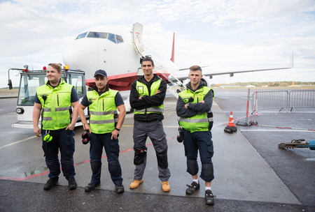 Ground Team With Arms Crossed Standing Against Airplane Archivio Fotografico