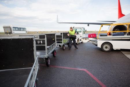 Worker Placing Luggage In Trailer On Runway