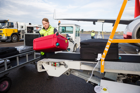 Lavoratore che scarica i bagagli dal trasportatore allegato all'aeroplano