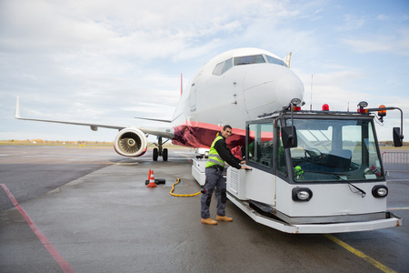 Worker Opening Towing Truck Attached To Airplane