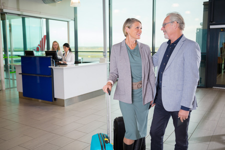 Senior Business Couple With Luggage In Airport