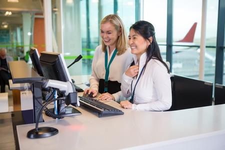 Receptionist sorridenti che lavorano alla scrivania nell'aeroporto