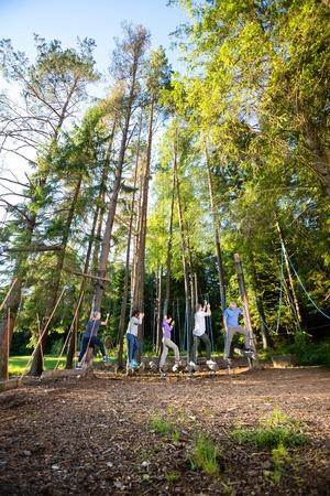 Gli amici multietnici che attraversano oscillano i ceppi nella foresta