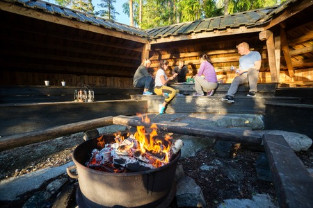 Burning Firepit With Friends Preparing Meal In Shed Archivio Fotografico