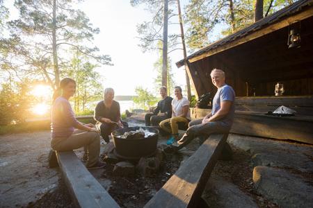 Amici sorridenti che cucinano alimento in Firepit alla foresta
