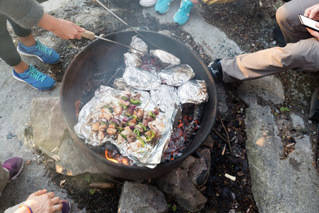 Friends Grilling Food In Firepit At Forest During Hike