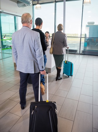 Passengers With Trolley Bags Waiting At Airport Reception Archivio Fotografico