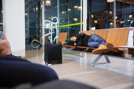 Young Man Sleeping In Airport Waiting Area