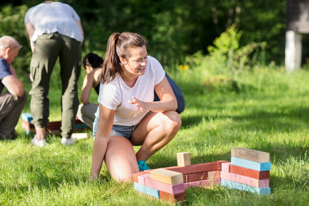 Woman Crouching By Building Blocks While Friends Planning In Bac