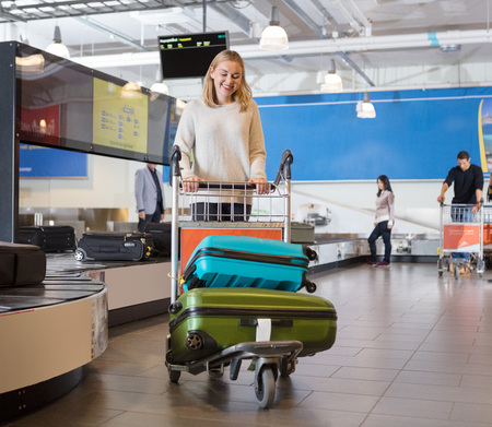 Young Woman With Luggage In Cart At Airport Archivio Fotografico