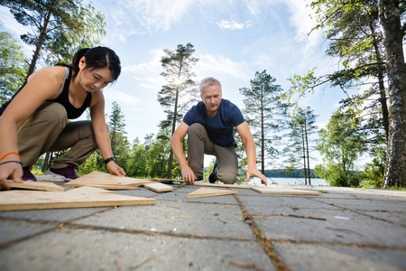 Friends Solving Puzzle With Wooden Planks On Patio