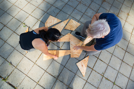 Directly Above Shot Of Friends Solving Wooden Planks Puzzle