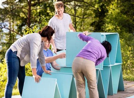Vrienden die Piramide van Planken op Terras in Bos maken