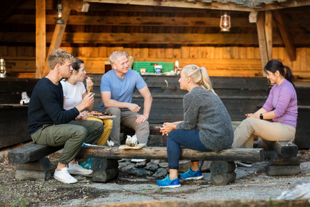 Business People Talking While Having Food By Shed In Forest
