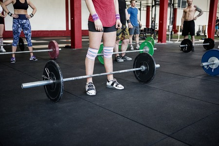 Low Section Of Instructor And Clients With Barbells
