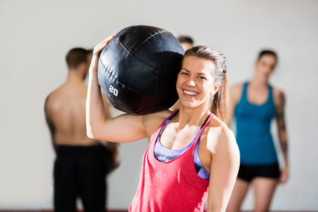 Smiling Female Trainer Carrying Medicine Ball